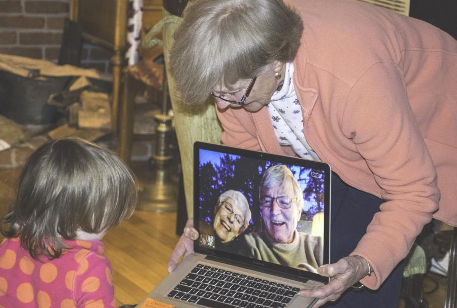 Ældre dame viser computer til barn